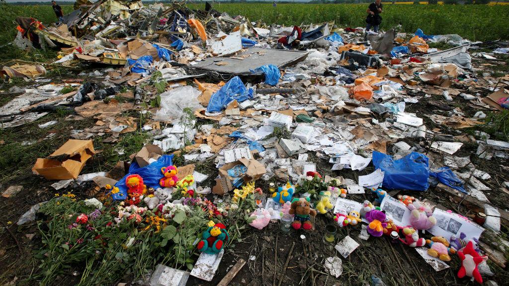 Flores y recuerdos dejados por residentes locales en el lugar del accidente del vuelo MH17 de Malaysia Airlines cerca del asentamiento de Rozspyne en la región de Donetsk, 19 de julio de 2014.