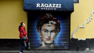 In this file picture taken on August 30, 2017 a woman walks past a mural of Mexican artist Frida Kahlo at Mesones street in Mexico City