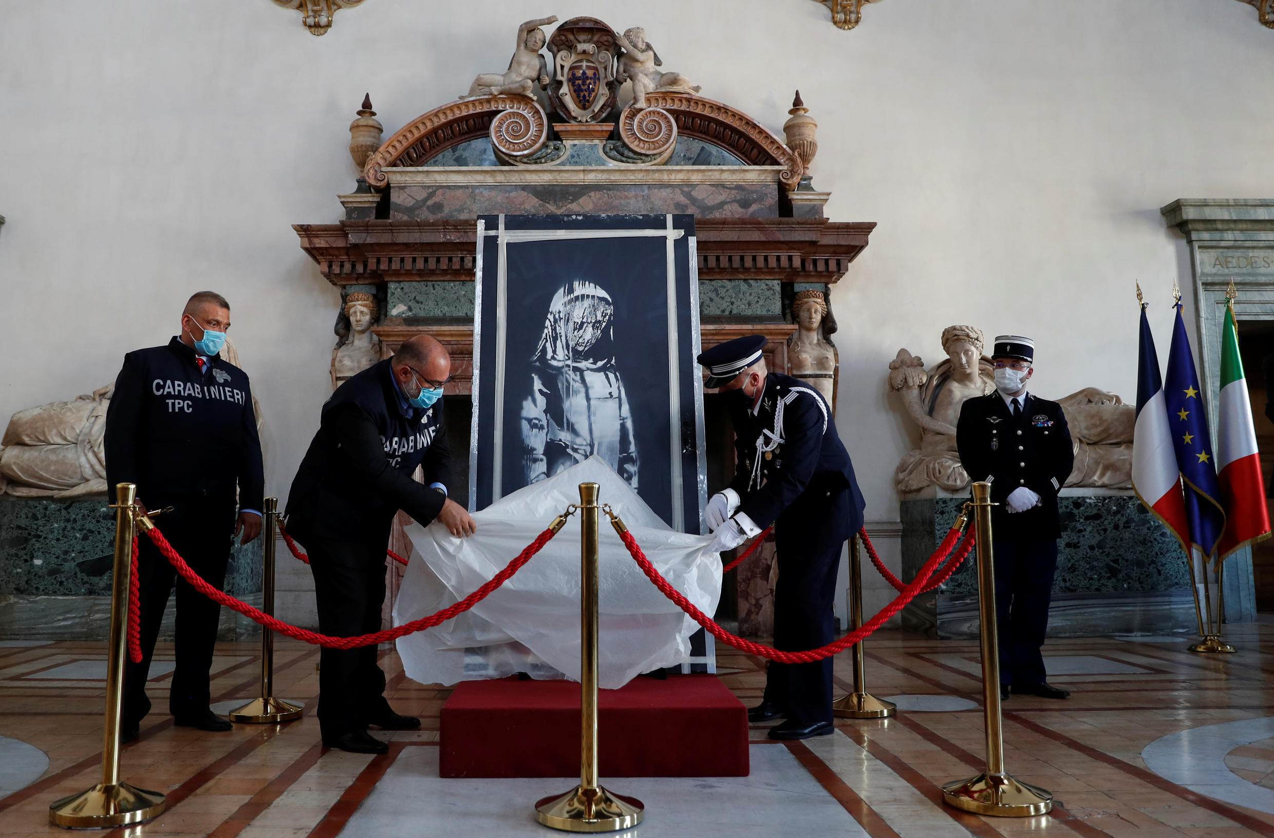 An Italian carabiniere and a French policeman unveil an artwork by British street artist Banksy during a ceremony at the French embassy in Rome, Italy, on July 14, 2020. The piece was stolen from the Bataclan concert hall in Paris and found in an Italian farmhouse.