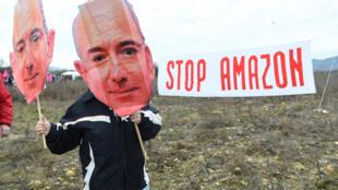 Un militant de l'association Attac tenant un masque du PDG d'Amazon, Jeff Bezos, lors d'une manifestation contre la construction d'un entrepôt de l'entreprise à Fournès (Gard), le 30 janvier 2021.