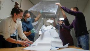 Los miembros de una comisión electoral local vacían una urna para comenzar a contar las papeletas de las elecciones municipales en Tomsk, Rusia, el 13 de septiembre de 2020.