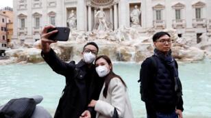 سائحان أمام نافورة ترافي في روما يرتديان الكمامات - إيطاليا 21/02/2020