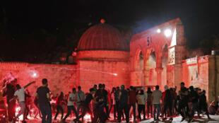 متظاهرون فلسطينيون يرشقون قوات الأمن الإسرائيلية بمقذوفات مشتعلة خلال مواجهات بين الطرفين في باحة المسجد الأقصى في القدس في 7 أيار/مايو 2021.