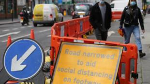 يافطة تشير الى تضييق الشارع لإعطاء فسحة أكبر للمارة في كامدن هاي ستريت وسط لندن في 11 ايار/مايو 2020