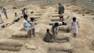 Los niños inspeccionan las tumbas preparadas para las víctimas del ataque aéreo del jueves en la provincia de Saada, Yemen. 10 de agosto de 2018.