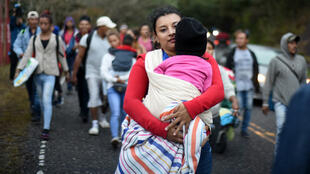 Honduran migrants walk in a caravan heading to the US, near Quezaltepeque, Chiquimula departament, Guatemala, on January 17, 2020. Hundreds of people in the vanguard of a new migrant caravan from Honduras forced their way across the border with Guatemala on Wednesday, intent on reaching the United States.
