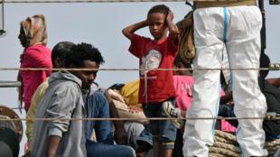"""Des migrants débarquent du navire militaire italien """"Sfinge"""" lors de leur arrivée dans le port d'Augusta sur la côte orientale de la Sicile, le 21 mai 2015."""