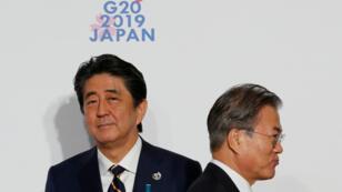 Le président sud-coréen Moon Jae-in (à d.) est accueilli par le Premier ministre japonais Shinzo Abe à son arrivée à Osaka, pour le sommet du G20, le 28juin2019.