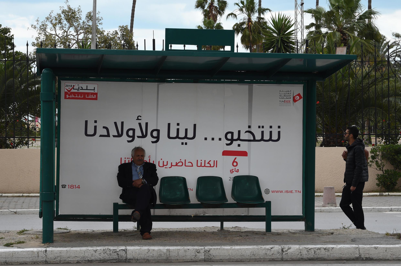 """""""Nous votons pour nous et pour nos enfants..."""": une affiche pour inciter les Tunisiens à voter, sous un abribus, le 4 mai 2018."""
