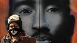 امرأة تضع كمامة تلتقط صورة لنفسها أمام جدارية لمغني الراب الراحل توباك شاكور في حي هارلم النويوركي في 5 أيار/مايو.