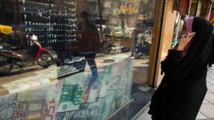 Una mujer observa los tipos de cambio en la ventana de una tienda de divisas en el distrito financiero de Teherán, Irán, 7 de enero de 2012.