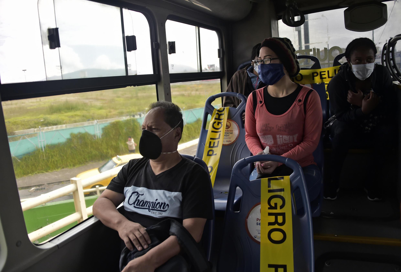 La gente se sube a un trolebús que ha bloqueado asientos como medida preventiva contra la propagación de COVID-19, en Quito, el 3 de junio de 2020, mientras Ecuador comienza a reabrir su economía en medio de la pandemia de coronavirus.