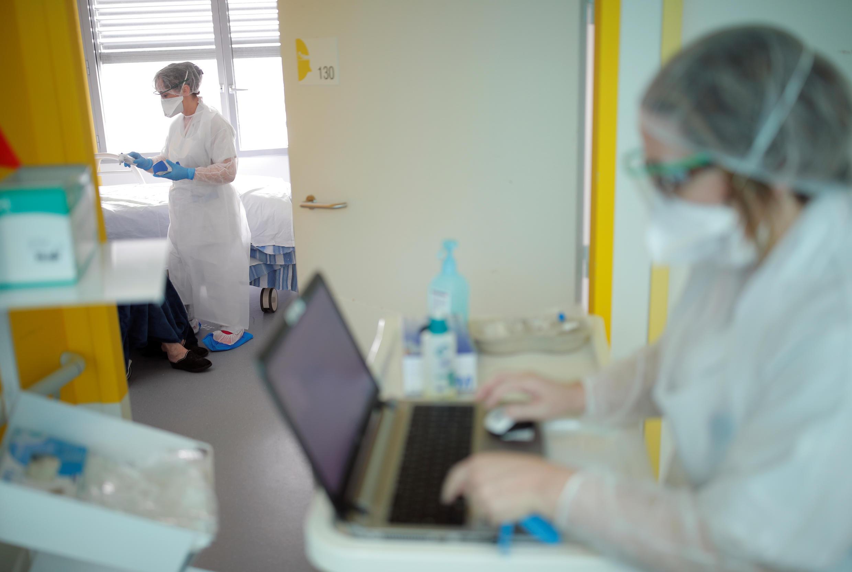 فردان من طاقم طبي بالملابس والأقنعة الواقية داخل وحدة علاج أمراض الرئة في مستشفى بمدينة فانس حيث يعالج مصابون بفيروس كورونا، فرنسا. 20/03/2020