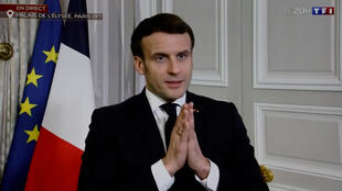 This photograph shows a television screen broadcasting French TV channel TF1 as French President Emmanuel Macron giving an interview from the Elysee Palace, following a video-conference meeting on Covid-19 vaccine production with pharmaceutical industry representatives, in Paris, on February 2, 2021.
