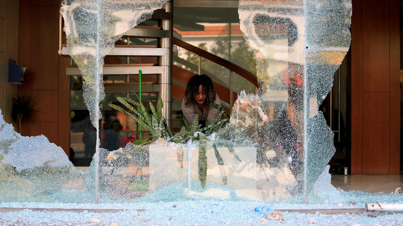 An employee cleans up after the window of a bank was broken during protests in Sidon on April 29, 2020.
