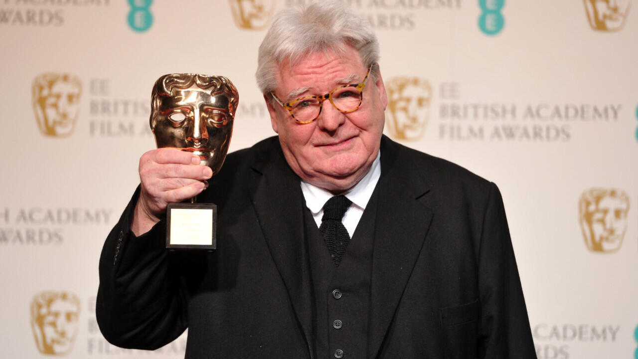 British film director, producer and writer Alan Parker poses with his BAFTA fellowship award during the annual BAFTA British Academy Film Awards at the Royal Opera House in London, UK, on February 10, 2013.