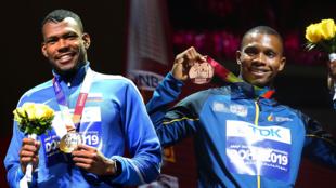 El ecuatoriano Álex Quiñónez y el colombiano Anthony Zambrano sonríen con sus medallas en el Mundial de atletismo en Doha, Qatar.