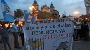 رجل يحمل لافتة تدعو الرئيس أوتو بيريز للاستقالة في مدينة غواتيمالا في 1 أيلول/سبتمبر 2015
