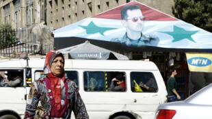 Une Syrienne passe devant un portrait du président Bachar al-Assad à Damas, en avril 2017.