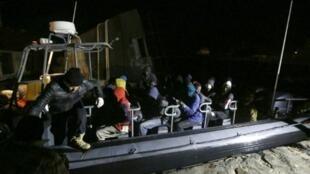 عناصر من قوات خفر السواحل الليبية يقومون بنقل مهاجرين تم إنقاذهم قبالة سواحل طرابلس في 5 شباط/فبراير 2017