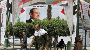 Los peatones caminan frente a una pancarta del presidente egipcio Abdel Fattah al-Sisi antes del próximo referendo sobre enmiendas constitucionales en El Cairo, el 16 de abril de 2019.