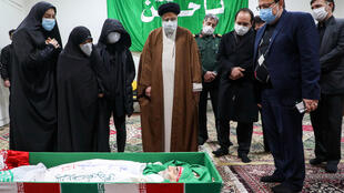 رئيس السلطة القضائية في إيران آية الله ابراهيم رئيسي (وسط) أمام جثمان العالم محسن فخري زاده بحضور عائلته في طهران في 28 تشرين الثاني/نوفمبر 2020