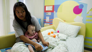 Thai surrogate mother Pattaramon Chanbua holds her baby Gammy, born with Down's syndrome, at the Samitivej hospital, Sriracha district in Chonburi province on August 4, 2014