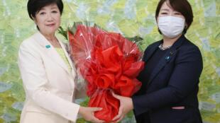 حاكمة طوكيو يوريكو كويكي (يسار) تتلقى باقة زهور في طوكيو في 5 تموز/يوليو 2020 بعد إعلانها فوزها بالاقتراع العام لاختيار حاكم العاصمة اليابانية.
