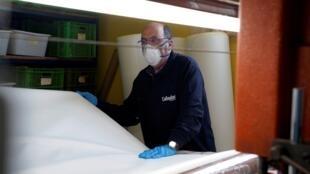 Un trabajador prepara tela para elaborar mascarillas sanitarias en la fábrica de zapatos Callaghan durante el brote de Covid-19 en Arnedo, España, el 23 de marzo de 2020.