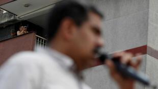 El personal de seguridad utiliza un monocular mientras que el presidente de Venezuela , Nicolás Maduro, pronuncia su discurso frente a sus simpatizantes durante un mitin de campaña en Charallave, Venezuela , el 15 de mayo de 2018.