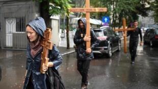 Manifestantes con cruces de madera protestan contra las medidas de confinamiento en Buscarest el 19 de julio de 2020
