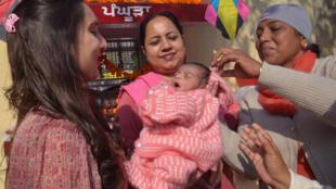 موظفون في الصليب الأحمر الهندي يحملون طفلة وليدة عثروا عليها ملقاة داخل صندوق في 12 يناير 2016