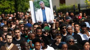 Des militants tenant un portrait d'Adama Traoré lors d'une marche blanche organisée en hommage à l'homme de 24 ans à Beaumont-sur-Oise, le 22 juillet 2016.