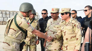 Egyptian President Abdel Fattah al-Sisi shakes hands with a member of the security forces during a visit to the Sinai Peninsula on July 4, 2015