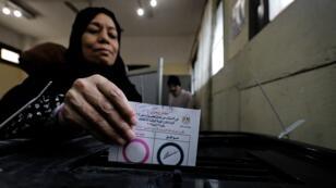 Une électrice égyptienne dépose son vote dans l'urne lors du référendum sur la révision constitutionnelle, au Caire, le samedi 20 avril2019.