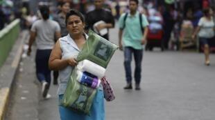 Una mujer carga rollos de papel higiénico este viernes en San Salvador, El Salvador el 13 de marzo de 2020.