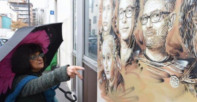 Lidya Tchilinkirian señala los retratos de los dibujantes de Charlie Hebdo que fueron desfigurados con bigotes de Hitler cerca de la antigua oficina del periódico satírico.