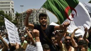 متظاهرون جزائريون يرفعون علم بلادهم خلال تظاهرة في العاصمة الجزائرية في 9 تموز/يوليو 2019.