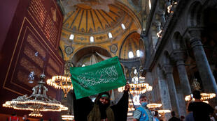 A woman holds a flag as she attends afternoon prayers and visits Hagia Sophia Grand Mosque, for the first time after it was once again declared a mosque after 86 years, in Istanbul, Turkey, July 24, 2020.