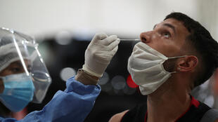 A healthcare worker takes a swab sample from a man to be tested forCovid-19 in Buenos Aires, Argentina on April 6, 2021.