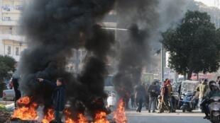 Des manifestants libanais brûlent des pneus lors d'une manifestation contre le gouvernement à Tripoli, au nord du pays, le 14 janvier 2020, pour dénoncer l'impasse politique et une crise économique paralysante.