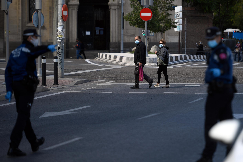Dos personas con mascarilla observan a los agentes de policía en Madrid, España, el 3 de octubre de 2020