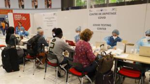 Des personnels de santé aident des voyageurs à remplir un questionnaire pour un test au coronavirus à leur arrivée à l'aéroport de Roissy-Charles-de-Gaulle, le 24 juillet 2020