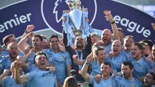 Manchester City et son entraîneur Pep Guardiola soulevant le trophée de Premier League, à Brighton le 12 mai 2019