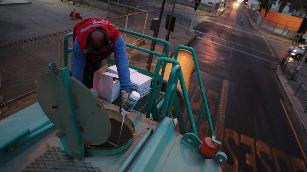 Un trabajador arroja compuestos de amonio cuaternario en un contenedor de agua de un camión utilizado en la industria minera, para desinfectar las calles en medio de la propagación del Coronavirus en Santiago, Chile, 12 de mayo de 2020.