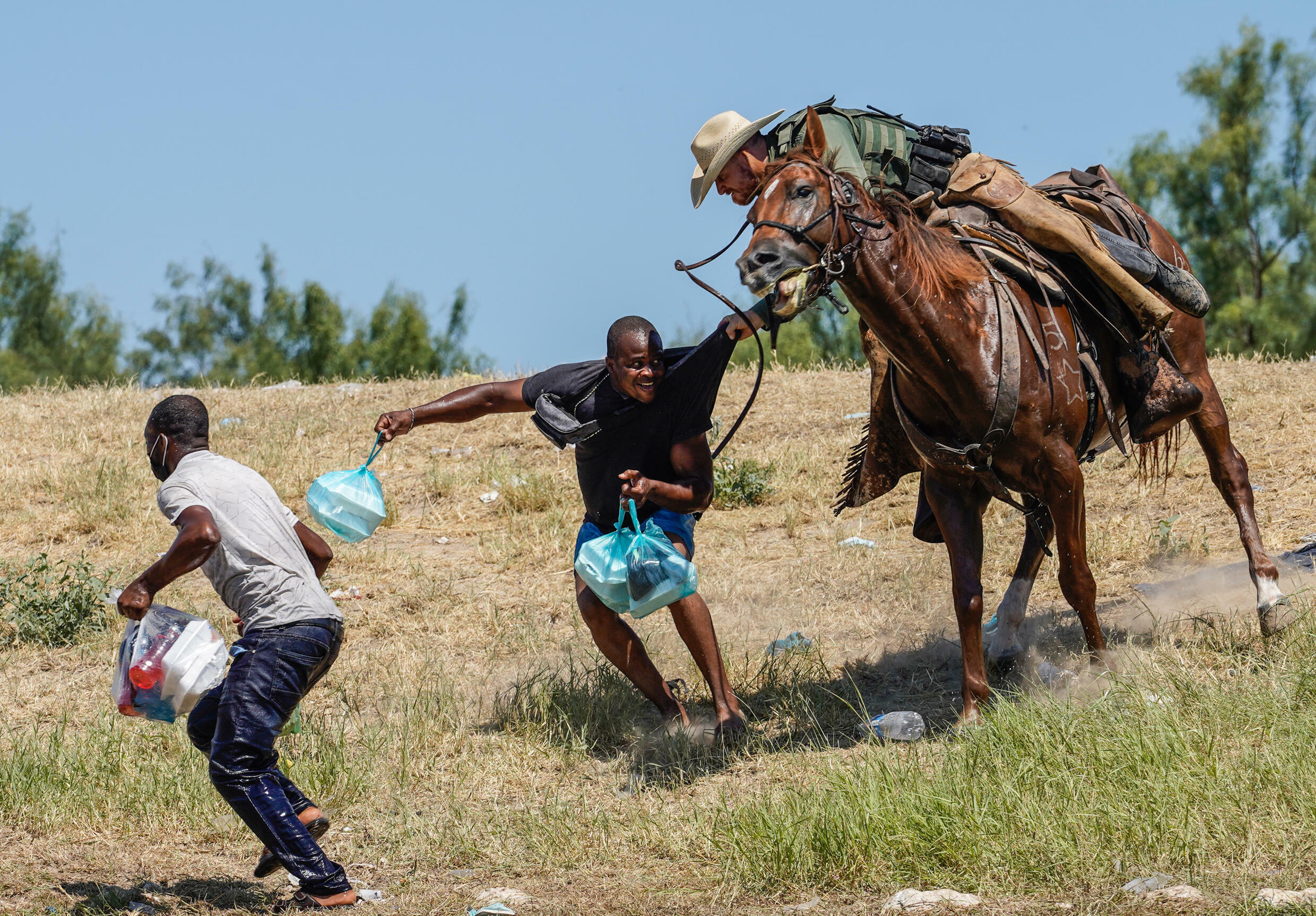 A United States Border Patrol agent on horseback tries to stop a Haitian migrant from entering an encampment on the banks of the Rio Grande near Del Rio, Texas