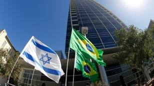 A picture taken on October 28, 2018 shows the Israeli and Brazilian flags flying outside the Brazilian embassy in Tel Aviv