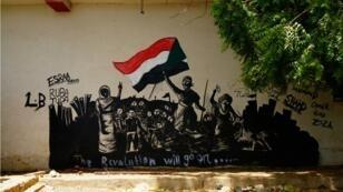 """Un graffiti """"La Révolution continuera"""" sur un mur de Khartoum, le 8 juin 2019."""