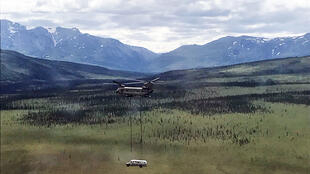 """In this image courtesy of the Alaska Army National Guard, a National Guard Chinook helicopter lifts Fairbanks Bus 142, made famous by the book and film """"Into the Wild,"""" from the remote Stampede Trail outside Denali National Park, near Healy, Alaska, on June 18, 2020. The bus was removed because of public safety concerns, since the remote and dangerous site had become a tourist attraction"""