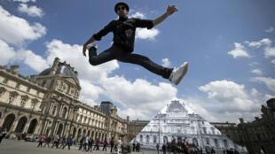 L'artiste JR près de son œuvre installée sur la pyramide du Louvre, le 25 mai à Paris.